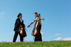 Two violoncellists play on grass against  sky Royalty Free Stock Photos