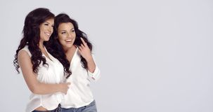 Two vivacious happy lady friends. With long wavy brunette hair standing arm in arm laughing and pointing towards blank copyspace on the right, on white stock footage