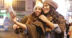 Two vivacious women taking a selfie. Two vivacious young women in trendy winter fashion standing close together outdoors in an urban street taking a selfie on a stock video footage