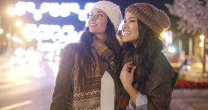 Two vivacious young women laughing and having fun. Two vivacious attractive young women in winter fashion standing outdoors in a brightly lit urban street stock video footage