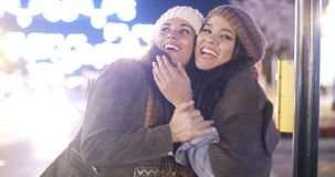 Two vivacious young women laughing and having fun. Two vivacious attractive young women in winter fashion standing outdoors in a brightly lit urban street stock footage