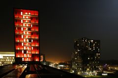 Two vivid lit buildings with the light of a city in the background and solor panels in the foreground stock image