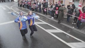 Two volunteer, waving pom pom, funny dance. Relay race of Sochi Olympic flame in Saint Petersburg. People. October 2013. Camera inside driving car stock footage