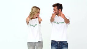 Two volunteers giving thumbs up to camera. On white background stock video
