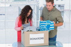 Two volunteers taking out clothes from a donation box Stock Photo