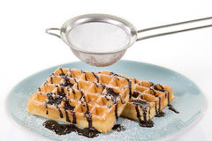 Two Waffles with chocolate on a blueish plate. Some powdered sug Stock Image