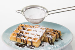 Two waffles with chocolate and powdered sugar on a blueish plate Stock Images