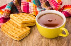 Two waffles, cup of tea and checkered napkin on table Royalty Free Stock Images