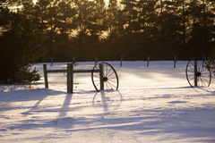 Two wagon wheels leaning against fence posts. On snow covered ground Stock Photos