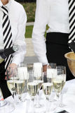 Two waiters fill glasses of champagne. At a party Stock Image