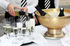 Two waiters fill glasses of champagne. At a party Royalty Free Stock Photos