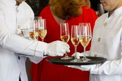 Waiters tray white wine. Two waiters hold a tray of white wine, champagne and water stock photo