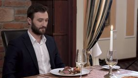 Two waiters simultaneously opens tableware cover - cloche showing the dish in front of the respectable bearded man in a suit. Fine stock video