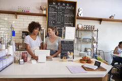 Two waitresses at a coffee shop looking at each other Stock Photo