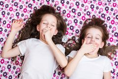 Two waking up yawning girls and an alarm clock in between stock photos