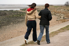 Two walkers on footpath. A couple walking arm in arm along windy footpath near estuary coast Stock Image