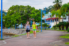 Two walking girls. Girls walking in the beautiful park among palm trees in Samana, Dominican Republic Royalty Free Stock Photos