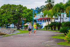 Two walking girls. Girls walking in the beautiful park among palm trees in Samana, Dominican Republic Royalty Free Stock Photo