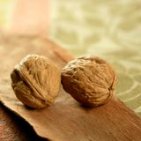 Two walnut over tablecloth. And wood royalty free stock photos