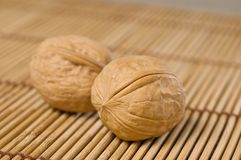 Two walnuts on bamboo mat. Royalty Free Stock Photos