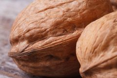 Two walnuts in the shell macro on an old wooden Stock Photography