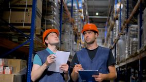 Two warehouse employees talk and take notes. stock video