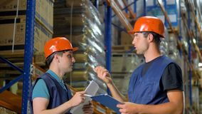 Two warehouse workers point and discuss storage items. stock video footage