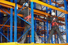 Two warehouse workers installing rack arrangement. Team of two warehouse workers in uniform with power tool drilling hole during rack arrangement erection work Royalty Free Stock Images