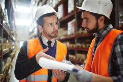 Two Warehouse Workers Reviewing Goods. Portrait of warehouse worker talking to supervising manager while doing inventory control in entrepot Two Warehouse royalty free stock images