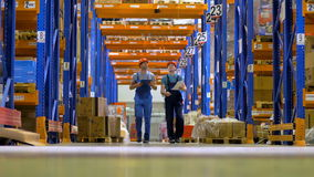 Two warehouse workers walk under high orange storage racks.