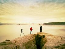 Two warm coat photographers with tripod shoot pictures of autumnal landscape below mountain. Royalty Free Stock Image