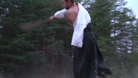 Two warriors in a kimono fight against each other on traditional Japanese weapons. Samurai find out who fights better, shooting in a coniferous forest stock video footage