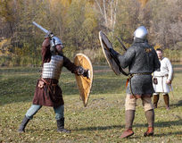 Two warriors in old Russian armors fight with swords and shields Royalty Free Stock Images