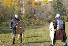 Two warriors in old Russian armors redy to reconstructed medieval fight with swords and shields royalty free stock image