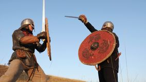 Two warriors Viking are fighting with swords, with lids, shields in the meadow. Two warriors Viking are fighting with swords, with lids and shields against the stock footage
