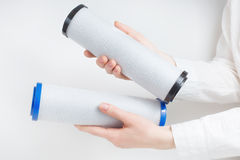 Two water filter cartridges in human hands. On white Stock Image