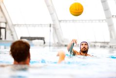 Two water polo players in a swimming pool. Men doing sport Royalty Free Stock Photography