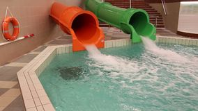 Two water slides. Green and orange - jets sliding down stock video footage
