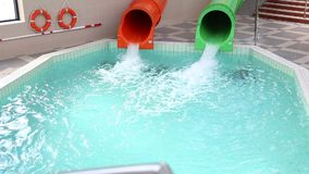 Two water slides. Green and orange - jets sliding down stock footage