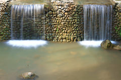 Two Waterfalls. Two small waterfalls separated by a stone wall.nn Royalty Free Stock Images