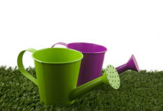 Two watering cans. On grass and white royalty free stock photos