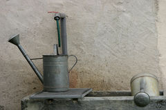 Two watering cans. In a fountain stock photos
