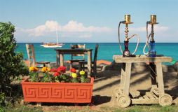 Two waterpies in outdoor restaurant in Turkey. Two traditional turkish waterpipes (nargile) on the table in outdoor restaurant with view on Mediterranean sea in Royalty Free Stock Image