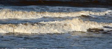 Two waves coming ashore on beach at Fleetwood. Two waves coming ashore on the beach at Fleetwood on the edge of Morecambe Bay, Lancashire, England on a windy royalty free stock photo