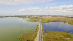 Two Way Road Between Lakes With Moving Cars. AERIAL VIEW. This is a shot over two way road situated between lakes and small land islands with several cars moving stock video