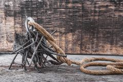 Two-way steel search magnet with rusty nails and old rope on wooden table. Text place Stock Photos