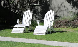 Two Weathered White Adirondack Chairs Symbols of Old Age, the Past, Time Passing, Togetherness. Two weathered Adirondack chairs sit empty in a sunny yard Royalty Free Stock Image