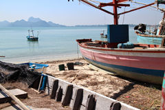 Two weathered wooden vintage fishing boats on shore at a calm bay in the sea along the Southern Coast of Thailand. A third smaller boat is visible just Royalty Free Stock Images