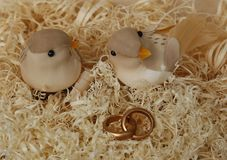 Two wedding birdies on wood shavings with wedding rings. A glass vase filled with yellow balls standing on a white table on a light background Royalty Free Stock Photography
