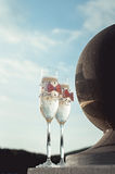 Two wedding champagne glasses with a bow on a stone railing. Lake promenade at sunset Royalty Free Stock Photos